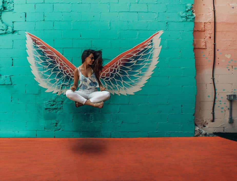 young-woman-floating-colorful-background-angel-wings