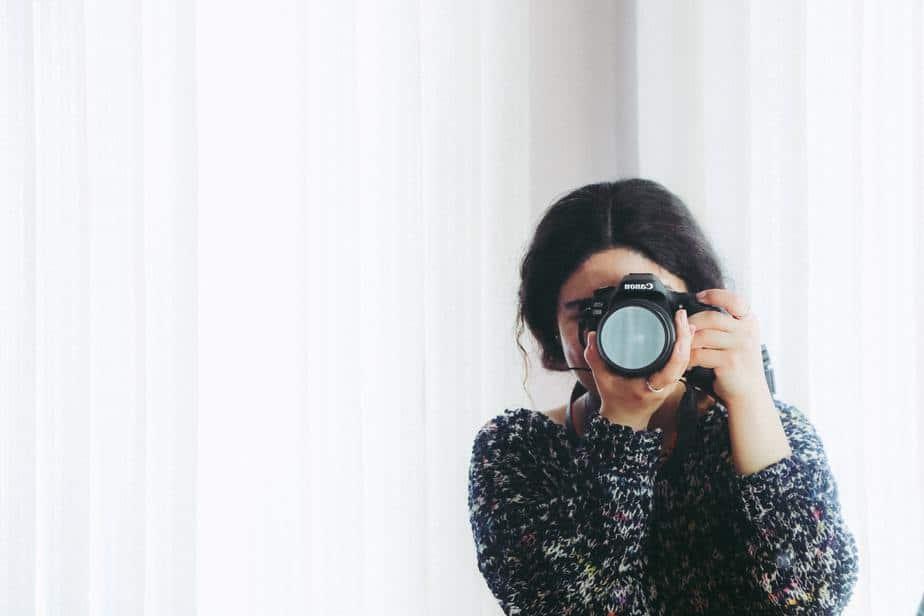 woman-holding-camera-white-background