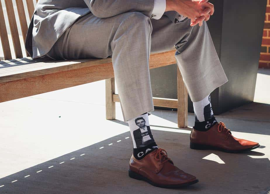 man-sitting-on-bench-funky-socks-brown-shoes