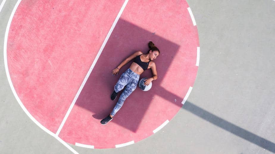 young-woman-lying-on-pink-court-with-ball