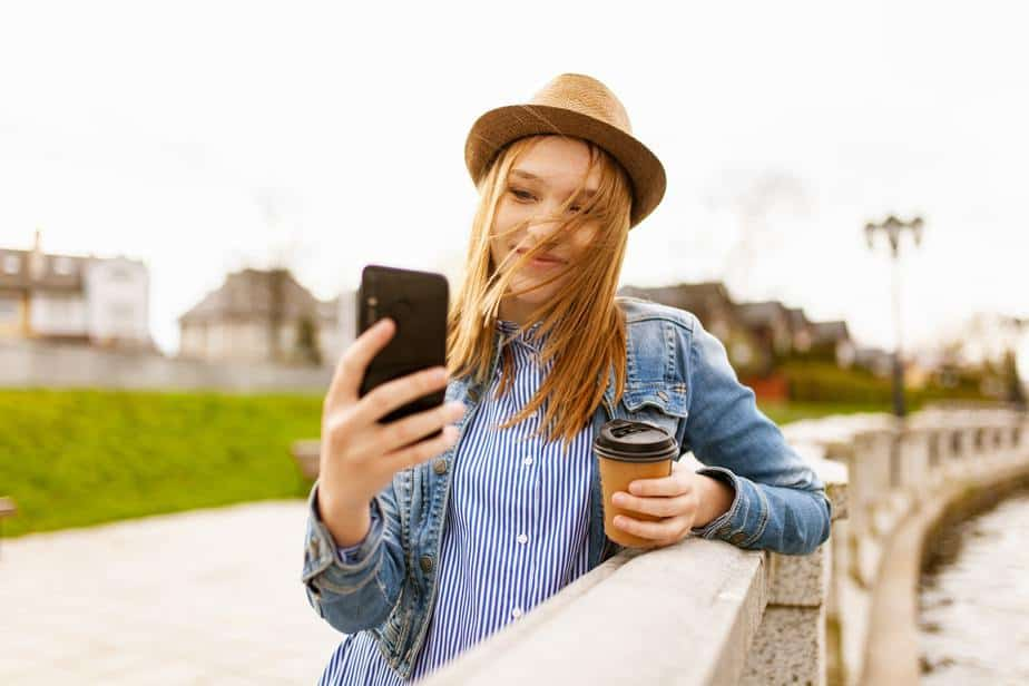young-woman-wearing-hat-with-cellphone-and-coffee