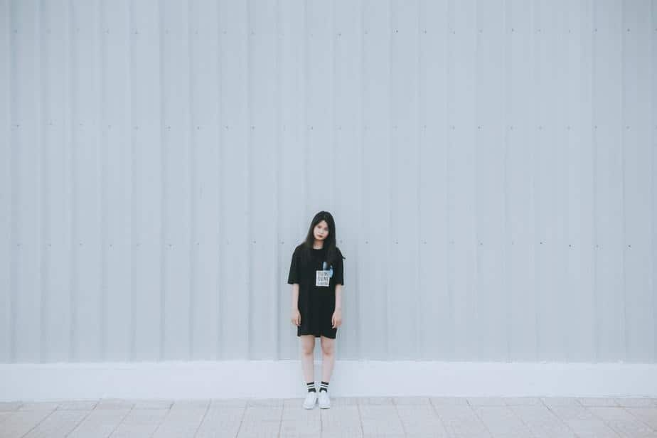 young-woman-wearing-black-standing-alone-white-wall