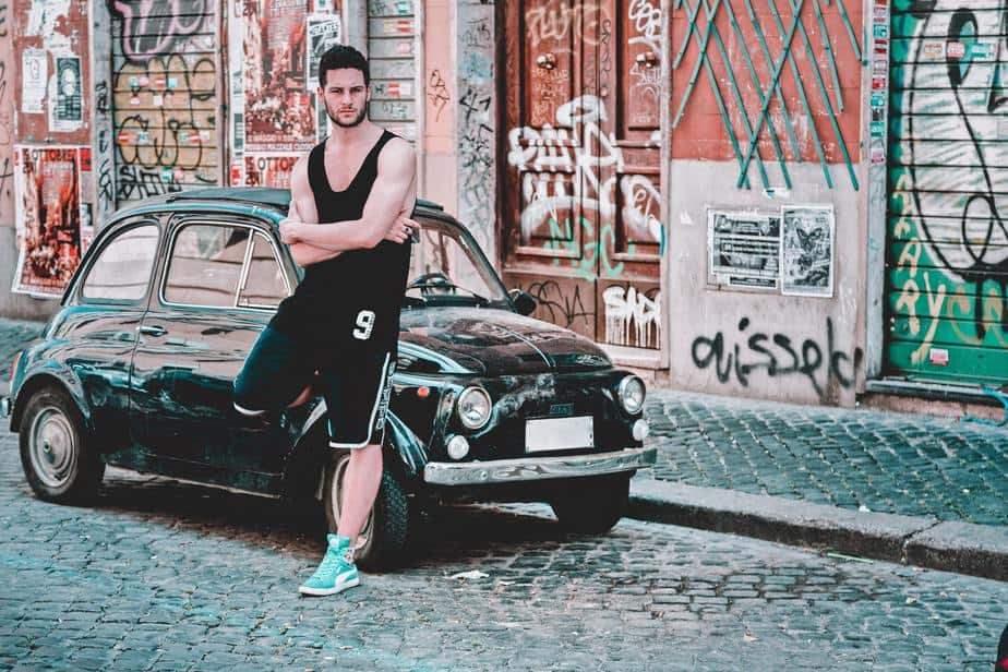 young-man-leaning-on-car-street-graffiti